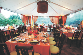 tables-covered-in-orange-tablecloths-and-various-bouquets-in-a-reception-tent