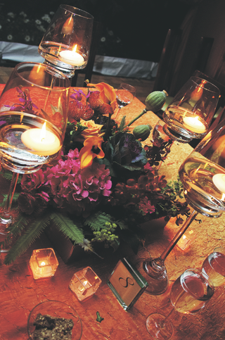 wedding-reception-table-decorated-with-fuchsia-and-orange-flowers-in-a-wood-box-surrounded-by-candle