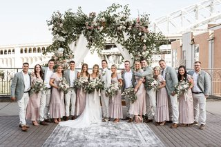 bride-and-groom-on-bridge-ceremony-with-bohemian-vintage-bridesmaid-dresses-grey-groomsmen-jackets