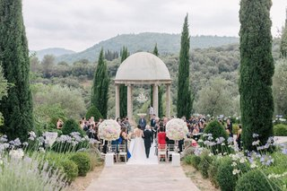 wedding-ceremony-in-south-of-france-outdoors-at-chateau-rotunda-large-flower-arrangements-aisle