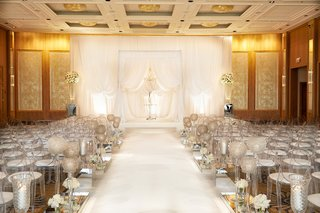 all-white-wedding-ceremony-with-white-drapery-arches-and-clear-ghost-chairs-with-white-cushions