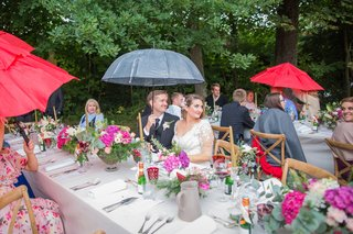 bride-and-groom-at-head-table-with-guests-rain-on-wedding-day-umbrellas-for-guests