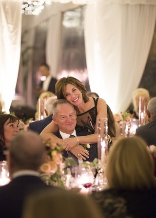 father-of-the-bride-sitting-at-table-while-the-mother-of-the-bride-bends-down-to-hug-him-from-behind