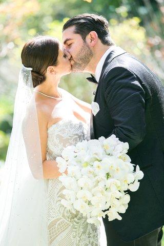 bride-in-leah-da-gloria-gown-bedazzled-veil-orchid-bouquet-kisses-groom