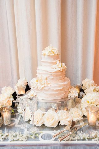 white-three-tier-wedding-cake-with-ruffle-details-fresh-gardenia-flowers-roses-at-base-candles