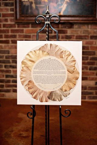 jewish-wedding-ketubah-with-golden-petals-to-form-a-flower-shape-on-iron-stand