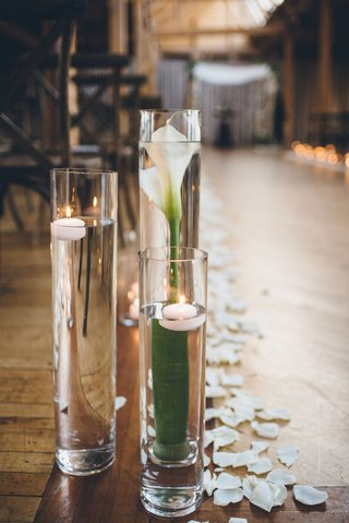 tall-vase-filled-with-calla-lily-and-floating-candles-submerged-wood-floor-rustic-ceremony-ideas