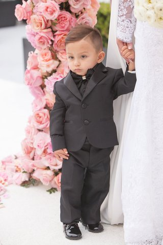 adorable-ring-bearer-in-black-suit-and-bow-tie-with-patent-leather-shoes-holding-moms-hand-bride