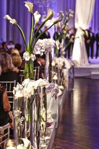 tall-glass-vases-along-aisle-filled-with-orchids-and-calla-lilies