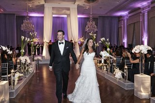 bride-and-groom-walk-up-aisle-holding-hands