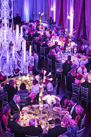 guests-at-dinner-service-under-chandeliers-and-purple-lighting