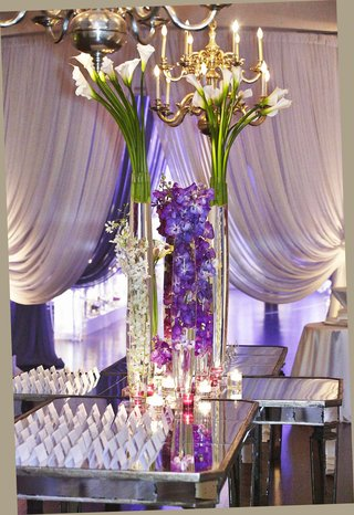 white-escort-cards-on-mirror-table-with-tall-flower-arrangements