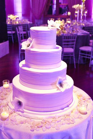 white-cake-with-purple-lighting-and-sugar-flowers
