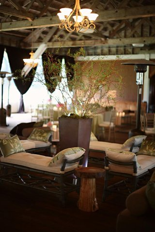 wooden-benches-topped-with-green-pillows-surrounding-tall-centerpiece-of-branches