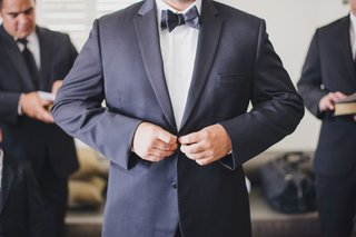 groom-buttoning-suit-jacket-with-black-bow-tie