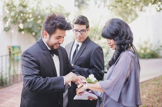 groom-puts-corsage-on-mother-in-purple-dress