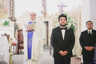 groom-watching-bride-walk-down-aisle-at-church-wedding