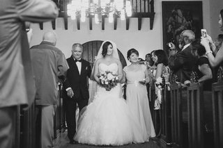 black-and-white-photo-of-bride-walking-down-aisle-with-parents