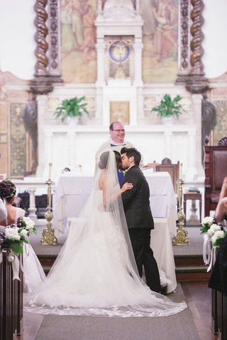 bride-and-groom-kiss-at-altar-of-catholic-wedding-church