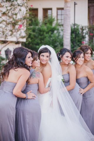 bride-smiling-with-bridesmaids-in-purple-strapless-dresses