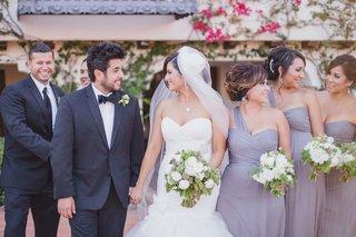 purple-bridesmaids-and-tuxedo-groomsmen-with-couple