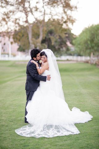 bride-and-groom-in-grass-after-wedding-ceremony