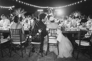 black-and-white-photo-of-bride-and-groom-kissing-at-outdoor-reception