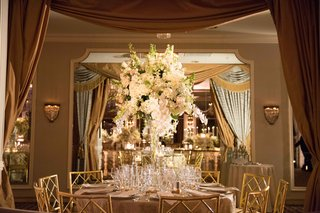 white-and-gold-tablescape-white-linens-gold-chairs-tall-cascading-floral-arrangement-white-greenery