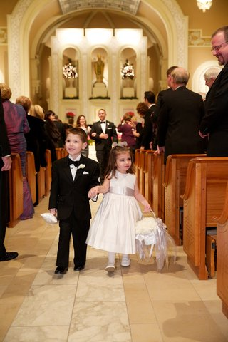 ring-bearer-in-a-black-tuxedo-and-bow-tie-and-flower-girl-in-sleeveless-white-dress-with-grey-sash