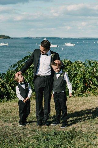 groom-posing-two-ring-bearers-little-tuxedos-bow-ties-green-black-white-maine-atlantic-ocean-peaks