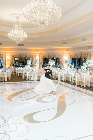 wedding-reception-oheka-castle-chandeliers-white-dance-floor-with-gold-monogram-regal-decor