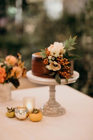 wedding-cake-small-on-cake-stand-chocolate-frosting-white-flowers-greenery-orange-berries