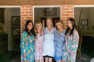bride-in-white-robe-and-bridesmaids-in-robes-with-pink-blue-purple-red-yellow-orange-flowers