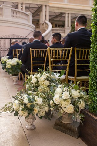 ceremony-on-patio-of-the-bellagio-flower-arrangements-in-stone-vases-at-base-of-aisle
