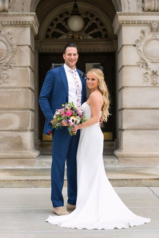 bride-in-strapless-lihi-hod-bridal-gown-carrying-colorful-bouquet-groom-in-blue-suit-floral-tie