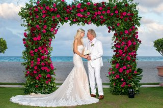 bride-in-strapless-wedding-dress-with-groom-in-white-suit-pink-shirt-under-greenery-arch-pink-roses
