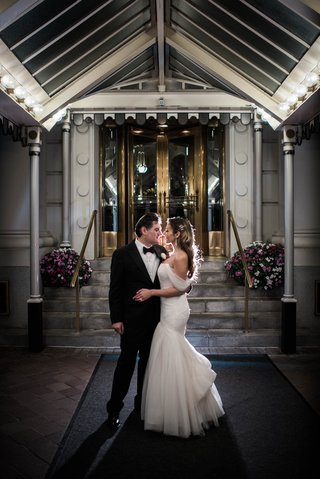 newlyweds-pose-in-front-of-hotel-venue-bride-in-monique-lhuillier-mermaid-off-the-shoulder-sleeves