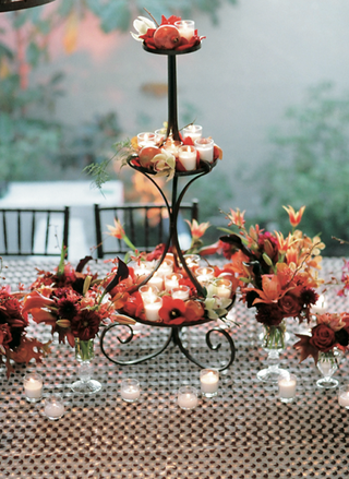 wrought-iron-tiered-stand-with-candles-and-red-flowers