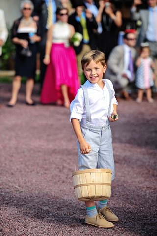 boy-in-short-pants-with-suspenders-and-white-shirt-holds-basket-at-country-wedding