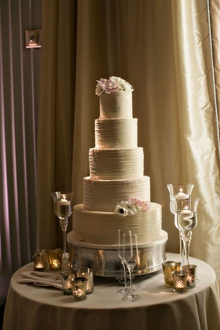 wedding-cake-five-layer-with-fresh-flowers-on-top-tier-and-bottom-tier-floating-candles-on-table
