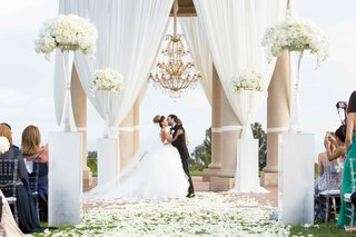 bride-groom-kiss-done-white-pillars-tall-arrangements-petals-chandelier-pelican-hill-newport-beach