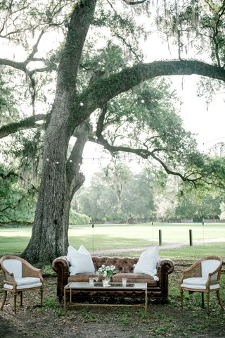 wedding-reception-lounge-area-under-tree-leather-chesterfield-sofa-white-wood-cane-armchairs-bistro