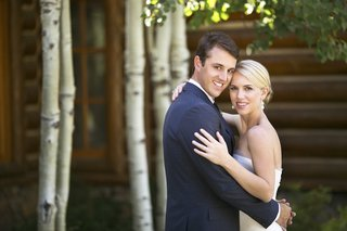 bride-and-groom-hugging-next-to-log-cabin-and-trees