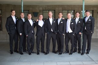 groom-and-groomsmen-in-black-tuxedos-and-white-vests-bow-ties