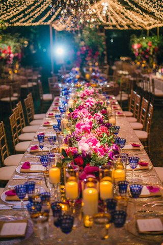 head-table-at-wedding-with-candlelight-pink-flowers-blue-goblets-and-twinkle-lights-overhead