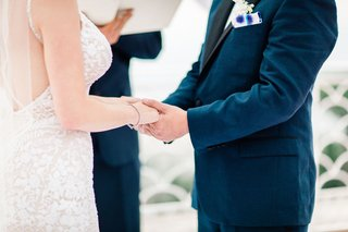 close-up-of-bride-and-groom-holding-hands-during-wedding-ceremony