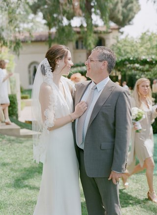 father-of-bride-in-grey-suit-smiles-at-bride-in-white-dress