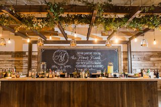 whiskey-bar-with-greenery-lights-and-chalkboard-wooden-bar