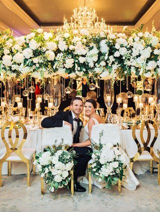 wedding-reception-elegant-ballroom-decor-bride-groom-chairs-white-fur-flower-greenery-gold-guest