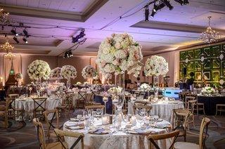 wedding-reception-ballroom-round-tables-vineyard-wood-chairs-tall-centerpiece-green-hedge-geo